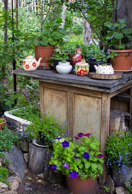 Nombreux pots de fleurs en décoration dans le jardin au printemps. fleurs décoratives sur une bûche au printemps Photo Premium