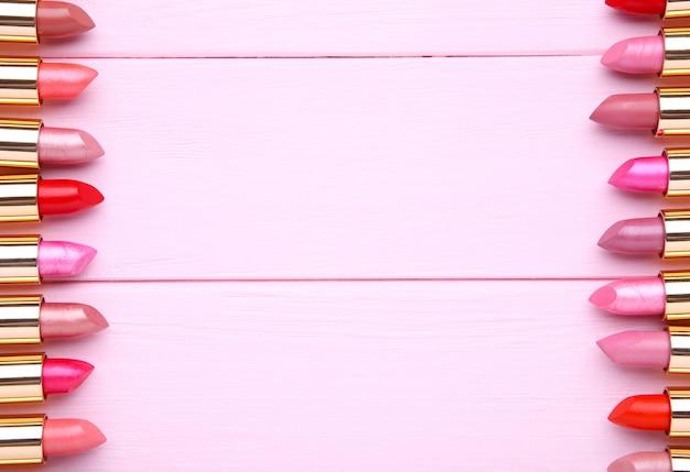 De nombreux rouges à lèvres colorés sur fond beige, poser à plat Photo Premium