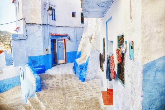 Nombreux souvenirs et cadeaux dans les rues de chefchaouen. peintures, tapis, vêtements Photo Premium