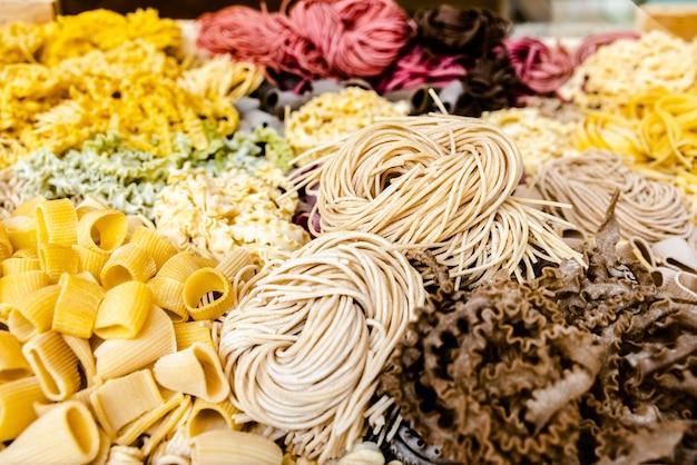 De nombreux types de pâtes italiennes non cuites de différentes couleurs et formes Photo Premium