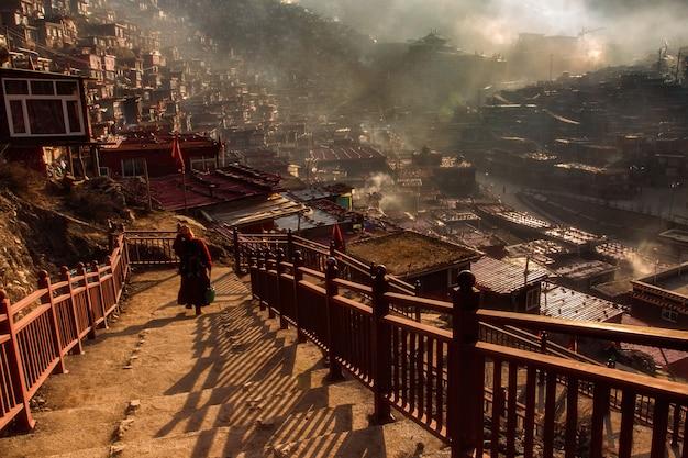 Nonne bouddhiste marchant dans l'escalier à larung gar dans une matinée chaude et brumeuse, sichuan Photo Premium