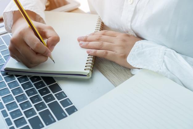 Note Asiatique D'étudiant Sur Le Cahier Tout En Apprenant L'étude En Ligne Ou L'apprentissage D'e Par L'ordinateur Portable Photo Premium