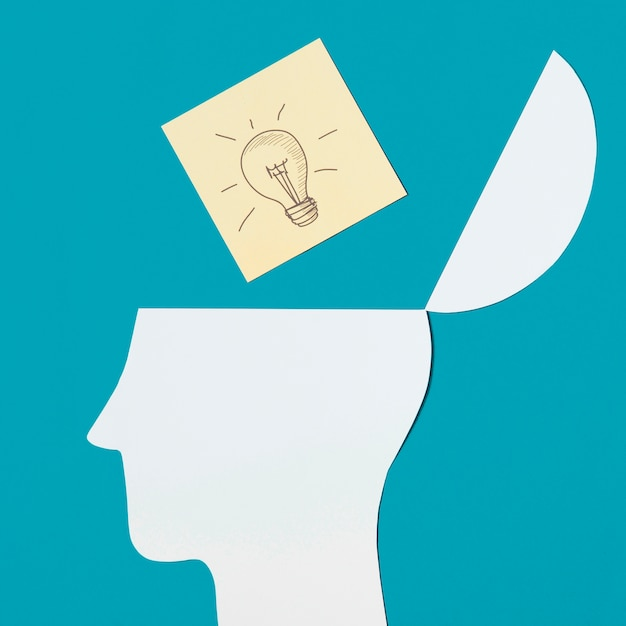 Note collante d'ampoule sur le papier ouvert découpé la tête sur fond bleu Photo gratuit