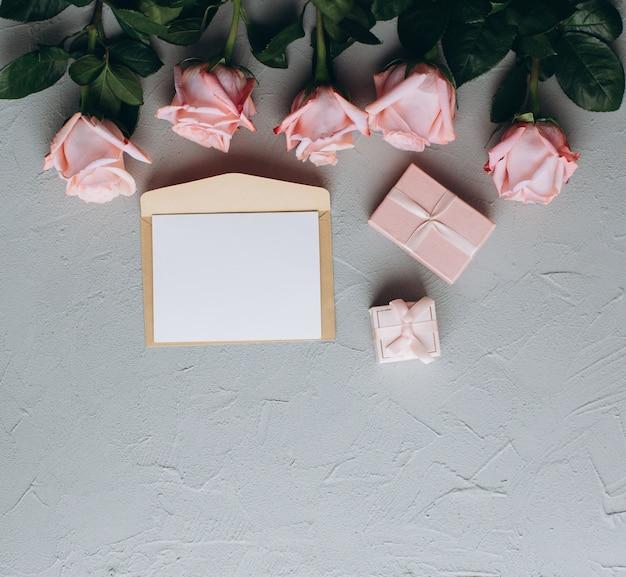 Note de papier blanc avec enveloppe, cadeaux et rose rose Photo Premium