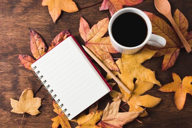 Notebook et café tasse sur fond de feuilles d'automne Photo gratuit