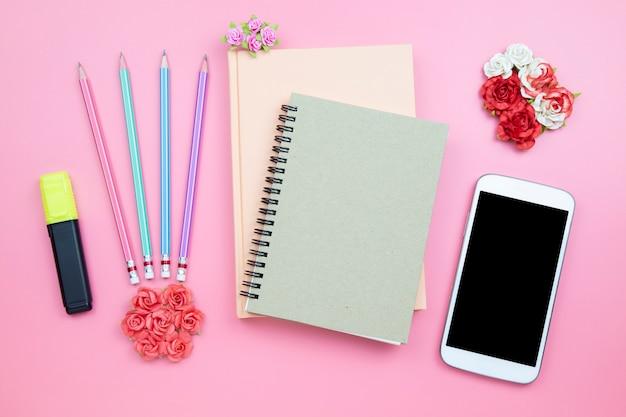 Notebook téléphone portable fleur rose sur fond rose style pastel Photo Premium