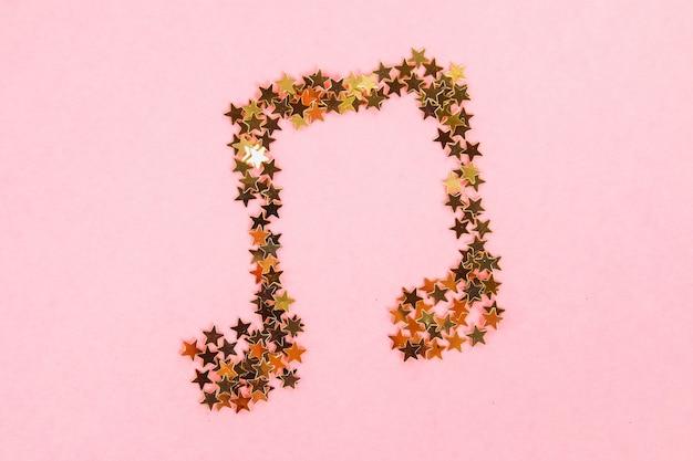 Notes de musique de confettis dorés étoilés se trouvant sur un fond rose pastel. Photo Premium