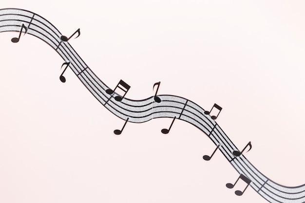 Notes de musique ondulées plates avec fond rose Photo gratuit