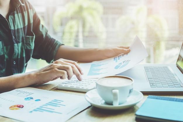 Notion de comptable. le comptable appuie sur la calculatrice pour calculer, vérifier l'exactitude du budget d'investissement en utilisant un ordinateur portable et des données de document à analyser. Photo Premium