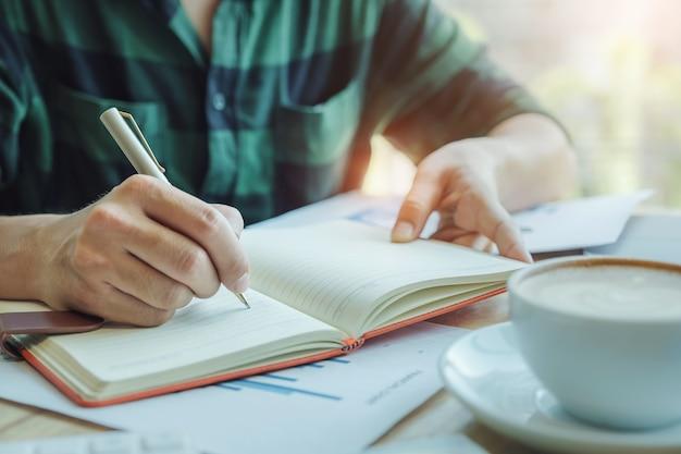 Notion de comptable. le comptable utilise un stylo pour noter les données afin de vérifier l'exactitude du budget d'investissement en utilisant un ordinateur portable et des données de document à analyser. Photo Premium