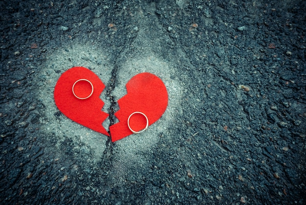 Notion De Divorce - Cœur Brisé Avec Des Anneaux De Mariage Sur L'asphalte Fissuré. Tonique Photo Premium