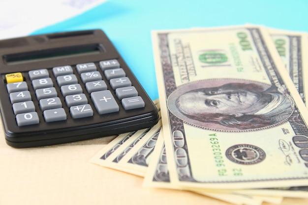 Notion de finance: les billets de cent dollars américains, une calculatrice, des factures. Photo Premium