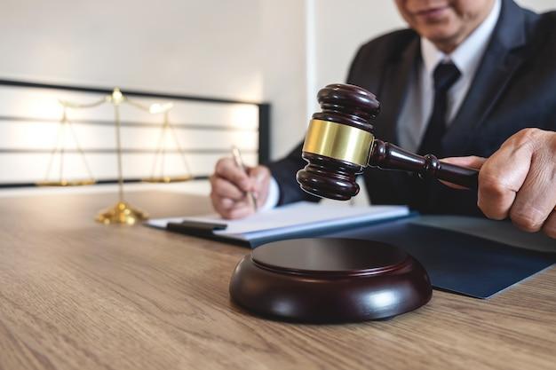 Notion juridique, de conseil et de justice, avocat-conseil ou notaire travaillant sur un document et un rapport sur l'affaire importante et un marteau en bois, échelle en laiton sur une table dans la salle d'audience Photo Premium