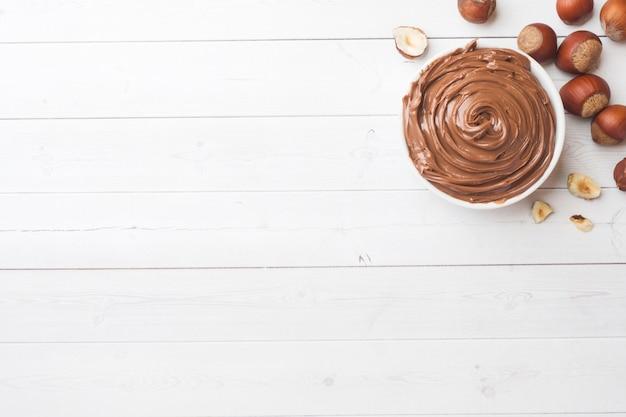 Nougat au chocolat dans une assiette sur un fond blanc avec des noisettes. Photo Premium