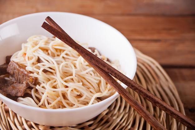 Nouilles Asiatiques Au Bœuf, Légumes Dans Un Bol Avec Des Baguettes, Fond En Bois Rustique. Dîner De Style Asiatique. Nouilles Japonaises Japonaises Photo Premium