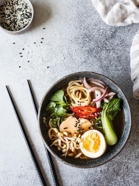 Nouilles asiatiques au ramen avec poulet, chou pak choi et œuf sur fond gris. Photo Premium
