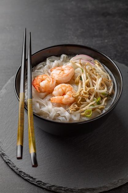 Nouilles asiatiques aux crevettes et fruits de mer dans un bol noir Photo Premium
