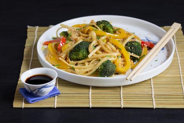 Nouilles Asiatiques Avec Légumes Et Sauce Soja Sur Tapis De Bambou Et Baguettes, Sur Fond Noir Photo Premium
