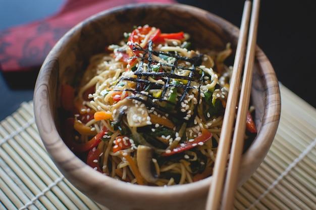 Nouilles aux légumes dans un bol en bois avec des baguettes en bois Photo gratuit