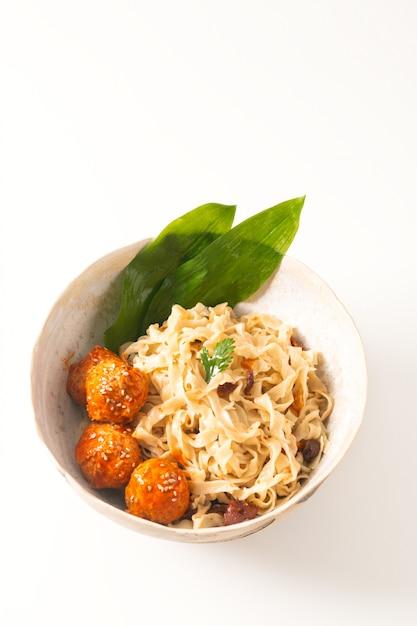 Nouilles aux oeufs oriental maison et boulettes de viande épicées dans un bol en céramique sur fond blanc Photo Premium