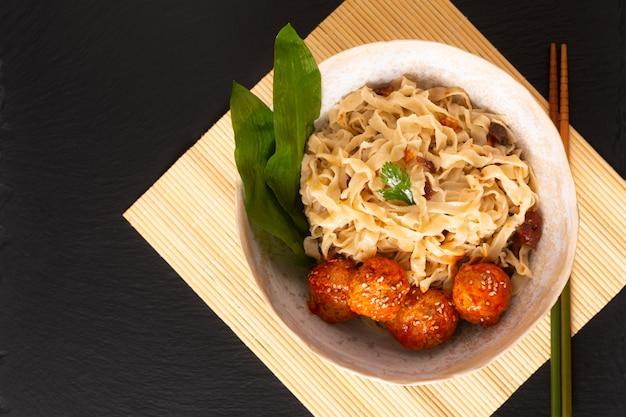 Nouilles aux oeufs oriental maison et boulettes de viande épicées dans un bol en céramique sur fond noir Photo Premium