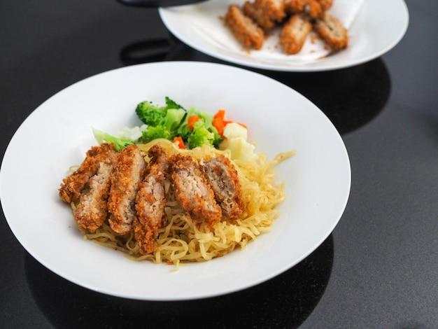 Nouilles aux œufs avec poulet frit et légumes Photo Premium