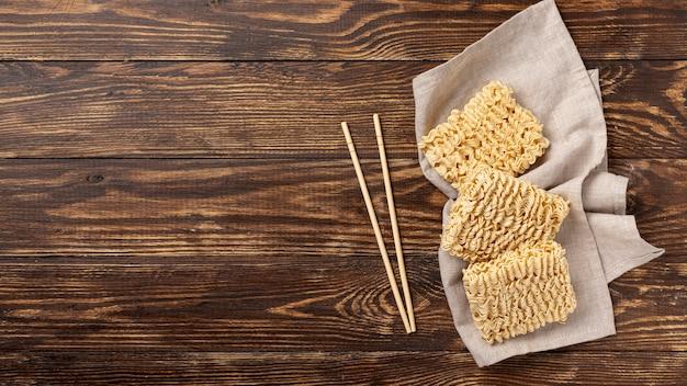 Des nouilles et des baguettes plates non cuites avec espace de copie Photo gratuit