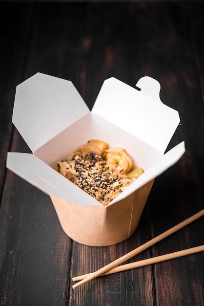 Nouilles en boîte avec graines de sésame et baguettes Photo gratuit