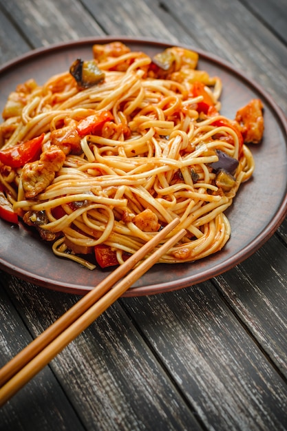 Nouilles chinoises à la sauce aigre-douce et baguettes sur la table Photo Premium