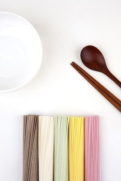Nouilles coréennes avec une cuillère en bois et des baguettes Photo Premium