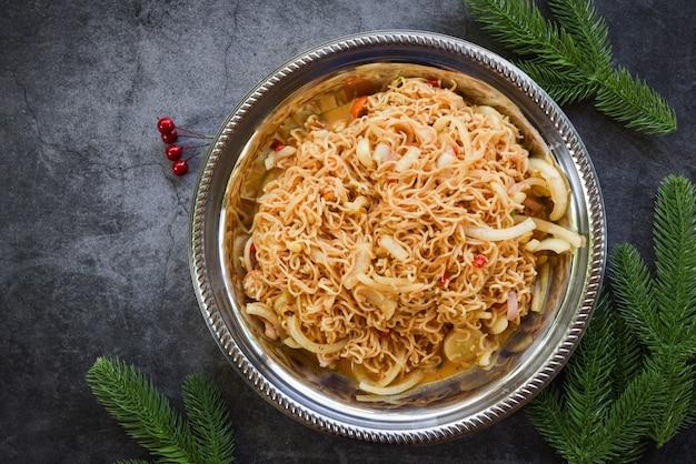 Nouilles instantanées cuites sur assiette - salade épicée aux nouilles avec des branches de sapin Photo Premium