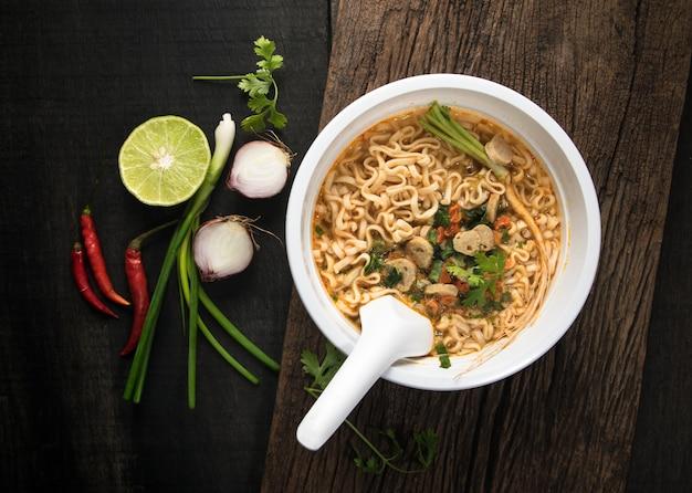 Nouilles instantanées dans un bol en plastique et plats d'accompagnement de légumes sur fond de bois. Photo Premium