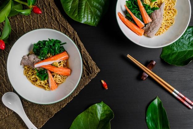 Nouilles instantanées épicées au bœuf et aux bâtonnets de crabe. vue de dessus Photo Premium
