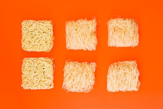 Nouilles instantanées non cuites disposées sur une surface orange Photo gratuit