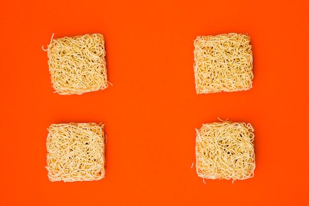 Nouilles instantanées sèches disposées sur une surface orange vif lisse Photo gratuit