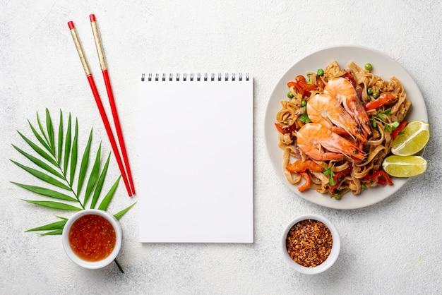 Nouilles plat poser avec des baguettes de crevettes et des légumes et des épices avec cahier vierge Photo gratuit