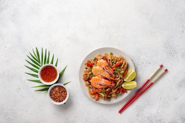 Nouilles plates avec légumes et crevettes avec des baguettes et des épices Photo gratuit
