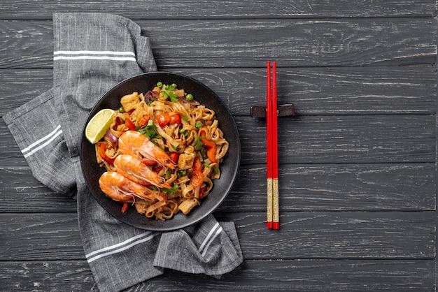 Nouilles plates avec légumes et poulet avec des baguettes Photo gratuit