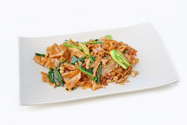 Nouilles et porcs plats sautés avec sauce de soja noire dans une assiette carrée Photo Premium