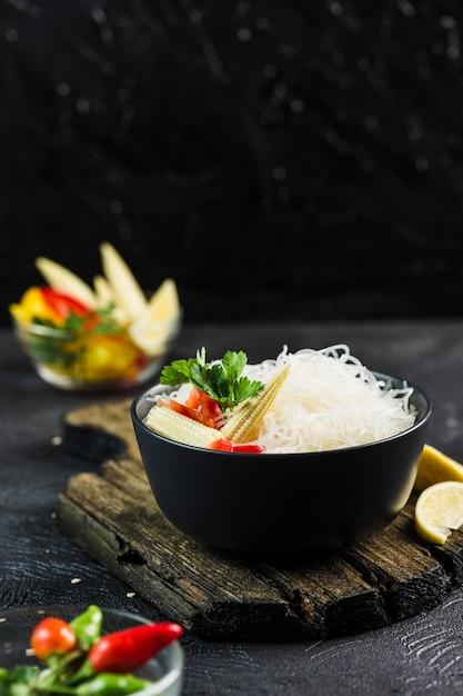 Nouilles De Riz Cellophane Aux Légumes Dans Un Bol Noir Avec Des Baguettes Sur Fond Sombre, Vue De Côté Agrandi. Photo Premium