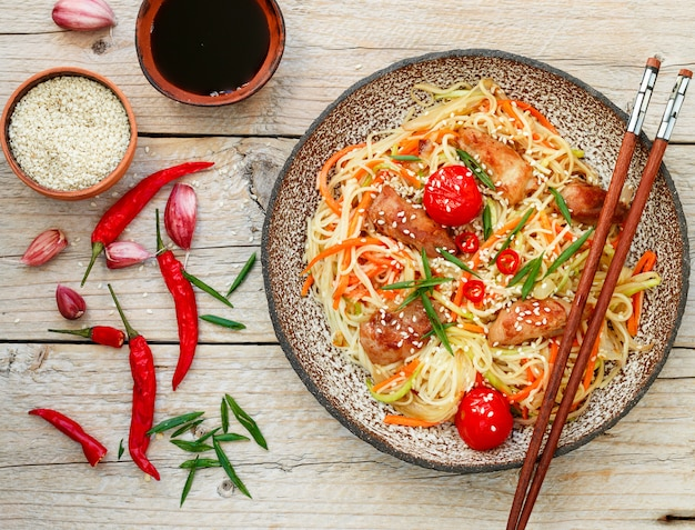 Nouilles sautées au poulet, légumes, graines de sésame et sauce soja sur plaque d'argile Photo Premium