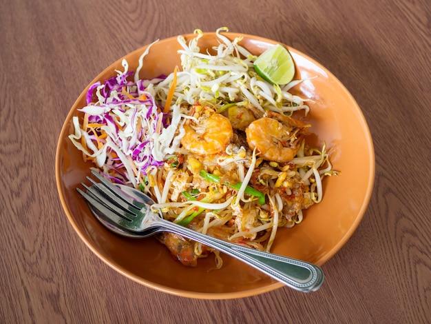 Nouilles sautées aux crevettes et légumes, pad thai sur une table en bois Photo Premium