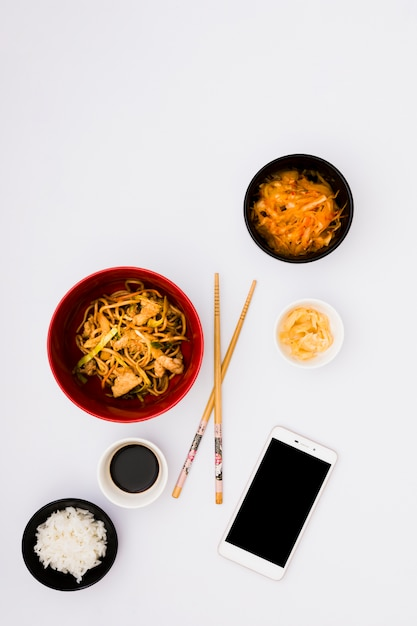 Nouilles savoureuses dans un bol près de la salade; cornichon au gingembre; sauce soja et riz cuit à la vapeur avec un téléphone portable sur fond blanc Photo gratuit
