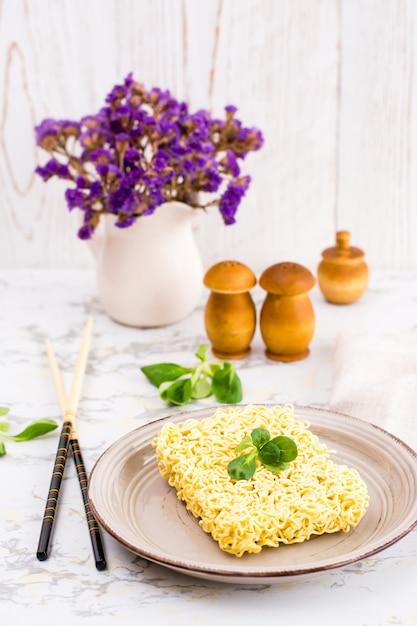 Nouilles sèches â'â hinese avec des feuilles de laitue sur une assiette en céramique et des baguettes Photo Premium