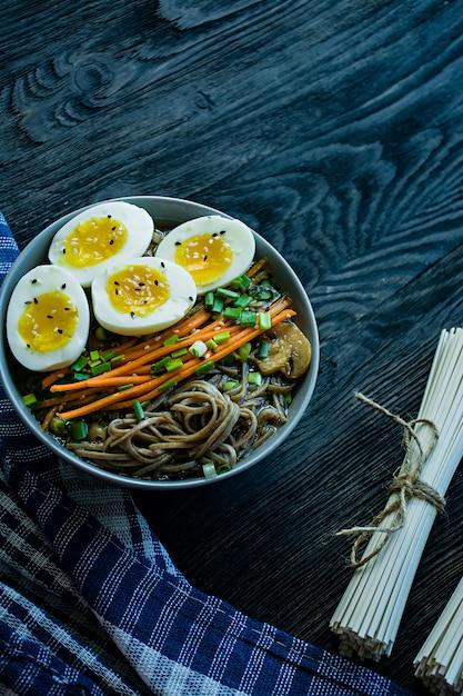 Nouilles soba au sarrasin avec sauce et accompagnements dans un bouillon. Photo Premium
