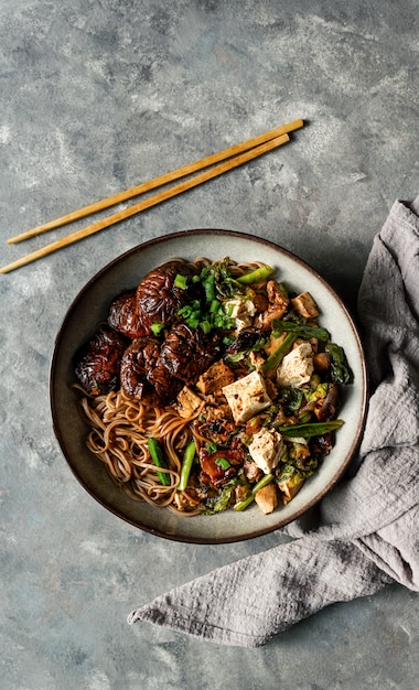 Nouilles soba végétaliennes asiatiques avec tofu, champignons shiitake Photo Premium