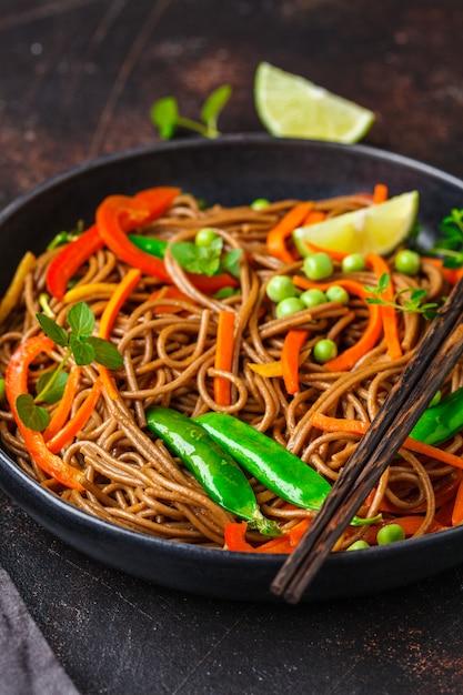 Nouilles Soba Végétaliennes Au Sarrasin Avec Légumes Dans Une Assiette Noire. Photo Premium