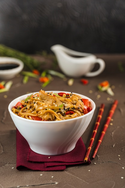 Nouilles Udon Au Poulet Et Légumes Dans Une Assiette Avec Des Baguettes Rouges Et De La Sauce Soja. Photo Premium