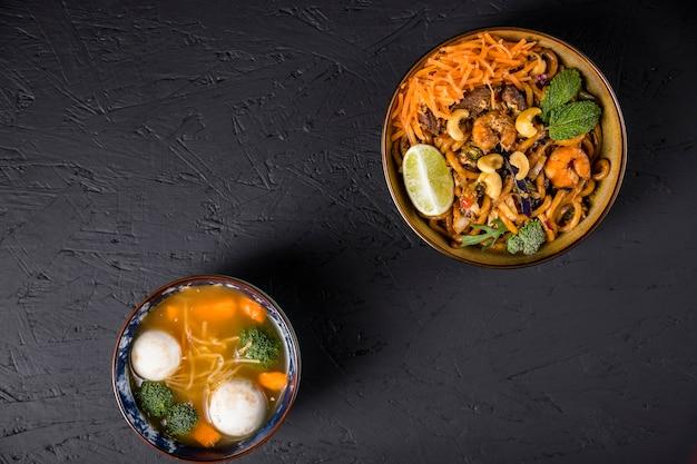 Nouilles udon frites avec boule de poisson et soupe de légumes sur fond texturé en béton noir Photo gratuit