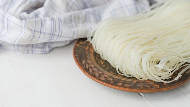 Nouilles de vermicelle de riz séchées sur une assiette circulaire près d'un chiffon à carreaux sur une surface blanche Photo gratuit